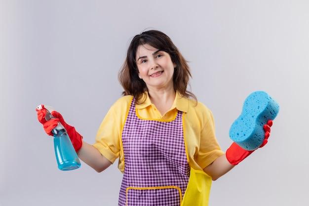 Vrouw die van middelbare leeftijd schort en rubberhandschoenen draagt die schoonmakende nevel en spons houden die vrolijk klaar om schoon te maken status over witte muur glimlachen