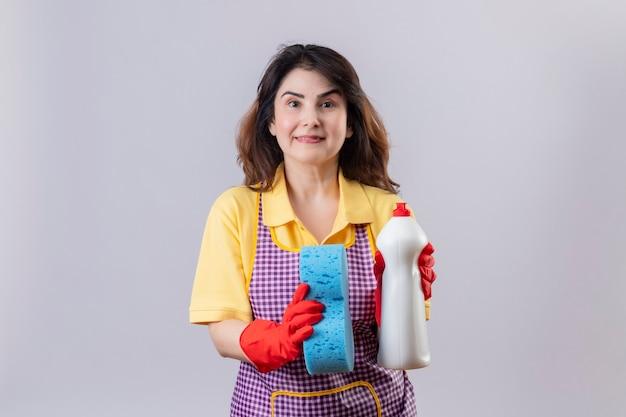 Vrouw die van middelbare leeftijd schort en rubberhandschoenen draagt die schoonmakende nevel en spons houden