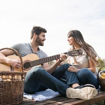 Vrouw die van muziek op gitaar geniet die door haar vriend bij picknick wordt gespeeld