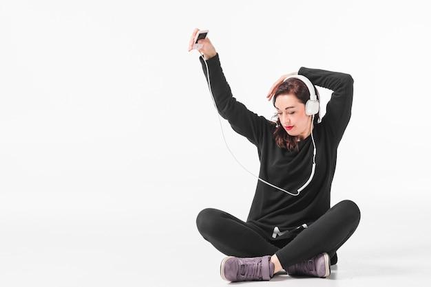 Vrouw die van muziek op mp3 speler geniet en tegen witte achtergrond danst