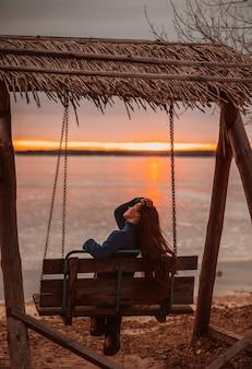 Vrouw die van tijd het ontspannen geniet door het mooie meer bij zonsopgang