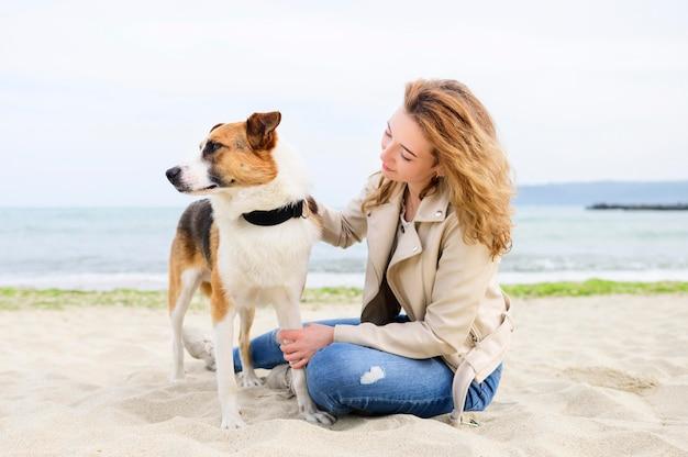 Vrouw die van tijd met haar hond in openlucht geniet