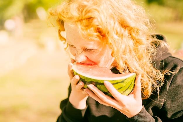 Vrouw die van verse sappige watermeloen in daglicht geniet