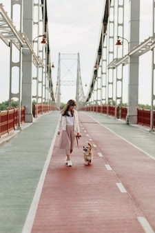 Vrouw die van volle lengte in heldere brug loopt die met corgi loopt