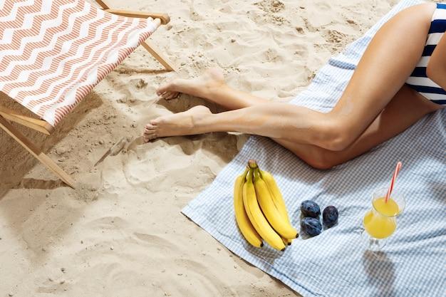 Vrouw die van vrije tijd geniet bij strand dat dranken en vruchten heeft