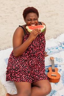 Vrouw die van watermeloen geniet bij het strand