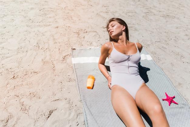 Vrouw die van zon op strand geniet