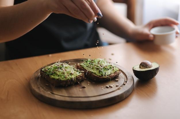 Vrouw die veganistische sandwich maakt met geroosterd roggebrood met guacamole-sesamzaadjes en zonnebloempitten. vrouw bestrooi met sesamzaadjes op sandwich