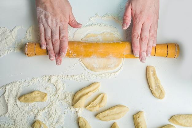 Vrouw die vegetarische bollen met aardappelpuree in de keuken koken