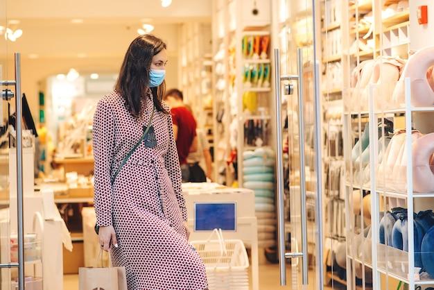 Vrouw die veiligheidsmasker draagt tijdens het winkelen en de covid2019-epidemie.