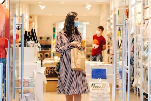 Vrouw die veiligheidsmasker draagt tijdens het winkelen. jonge vrouw met boodschappentassen in het winkelcentrum. mode, aankopen, winkelen en lifestyle-concept. covid-2019-epidemie. nieuw echt leven tijdens pandemie
