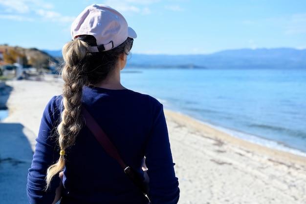 Vrouw die ver kijkt naar de blauwe zee in het dorp nea roda, halkidiki, griekenland