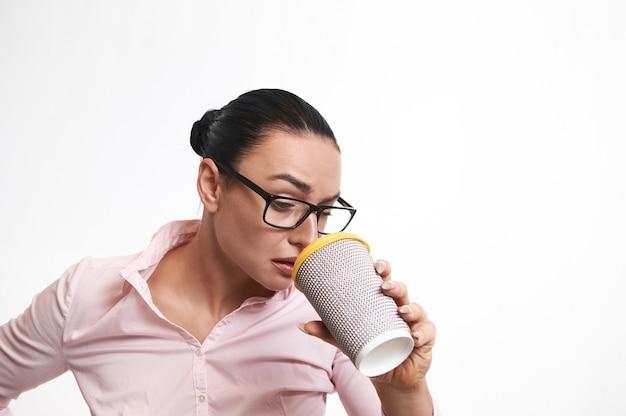 Vrouw die verbaasd en ontevreden kijkt door een kartonnen afhaalbeker voor warme dranken.