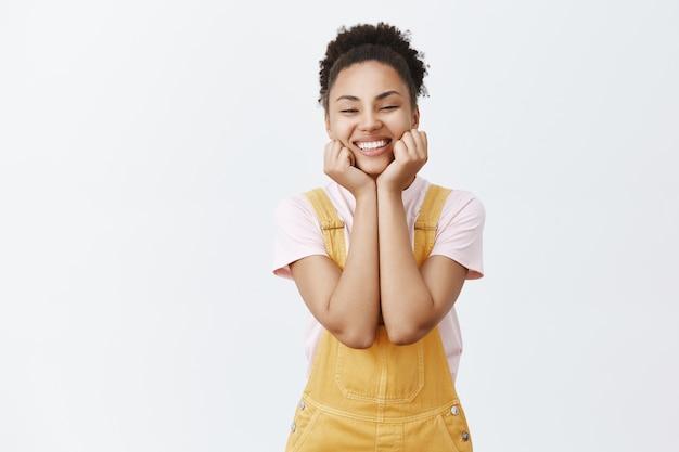 Vrouw die verliefd is. portret van charmante afro-amerikaanse mooie vrouw in gele trendy overall, palmen op de kin te houden en breed glimlachend