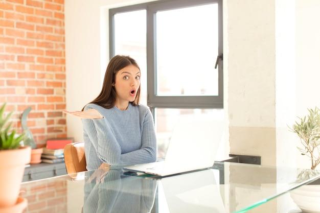 Vrouw die verrast en geschokt kijkt, met open mond en een object vasthoudt met een open hand aan de zijkant