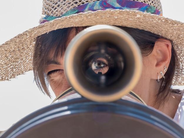 Vrouw die verrekijkers in de stad met behulp van
