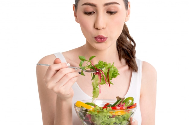 Vrouw die verse groentesalade in glaskom houdt die op witte achtergrond wordt geïsoleerd