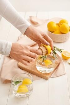 Vrouw die verse limonade in keuken maakt