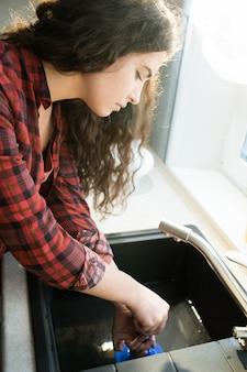 Vrouw die verstopte afvoeren met zuiger opruimt