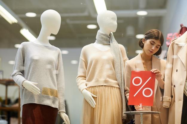 Vrouw die vertoning in kledingsopslag schikken
