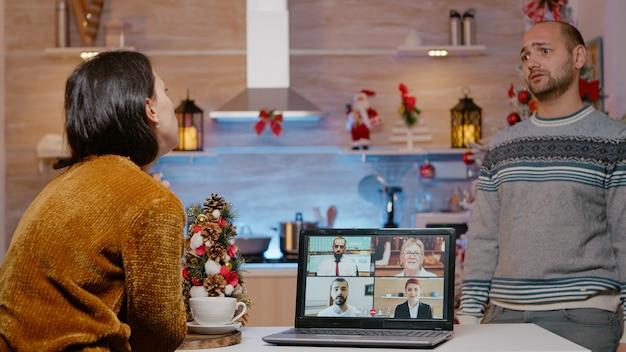 Vrouw die videogesprek gebruikt voor werkvergadering op kerstavond