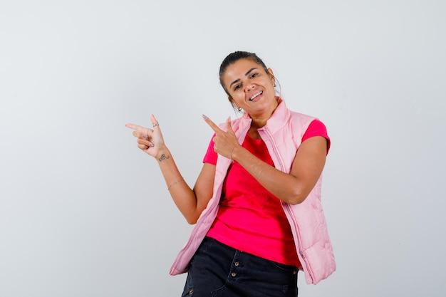 Vrouw die vingerpistool tekent in t-shirt, vest en er zelfverzekerd uitziet
