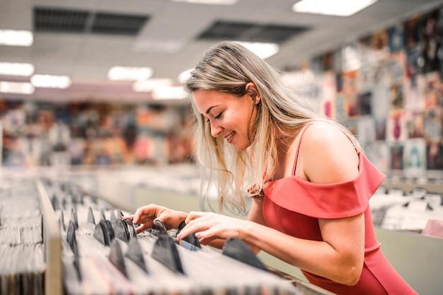 Vrouw die vinyl in een winkel selecteert
