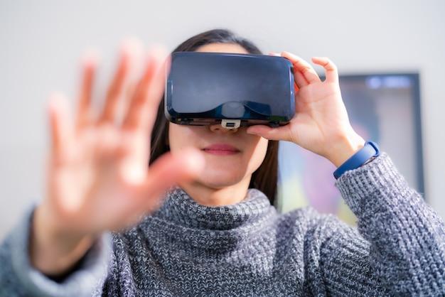 Vrouw die virtuele werkelijkheidsglazen draagt. smartphone gebruiken met vr-headset