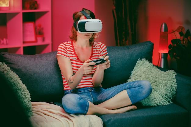 Vrouw die virtuele werkelijkheidsglazen testen terwijl het zitten op bank in huisbinnenland. kaukasisch wijfje met vrhoofdtelefoon op gezichts speelspel met glimlach op laag in moderne flat