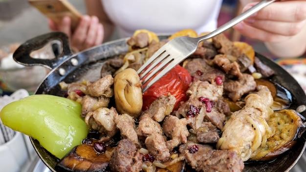 Vrouw die vlees eet met groenten geserveerd in koekenpan in restaurant close-up