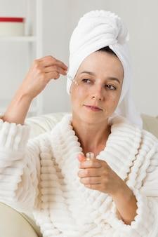 Vrouw die vochtinbrengende crème op haar gezicht toepast