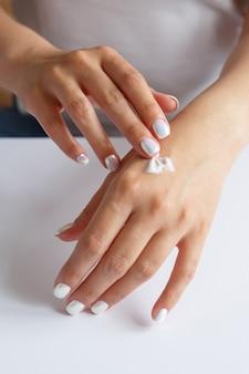 Vrouw die vochtinbrengende crème op haar handen toepast. hand huidverzorging. gezondheid en schoonheid concept