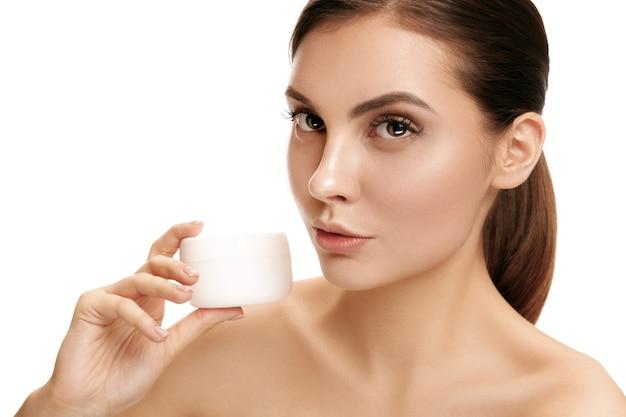 Vrouw die vochtinbrengende crème op het gezicht aanbrengt in de studio