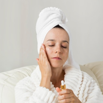 Vrouw die vochtinbrengende crème voor haar huid gebruikt