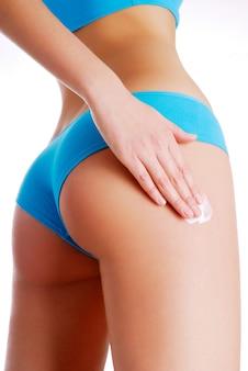 Vrouw die vochtinbrengende crèmeroom op benen toepast.