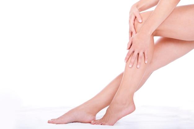 Vrouw die vochtinbrengende crèmeroom op de benen toepast