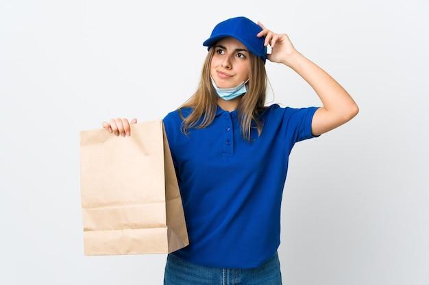 Vrouw die voedsel bezorgt en beschermt tegen het coronavirus met een masker op geïsoleerd wit met twijfels en met verwarde gezichtsuitdrukking