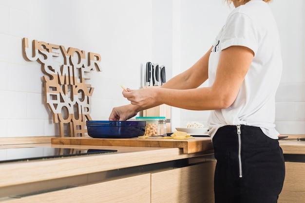Vrouw die voedsel in container in comfortabele keuken zet