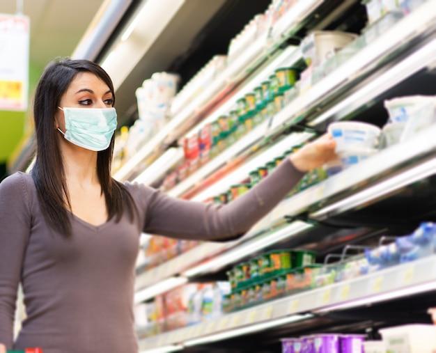 Vrouw die voedsel in een supermarkt koopt terwijl het dragen van een masker