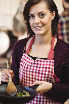 Vrouw die voedsel in keuken voorbereidt