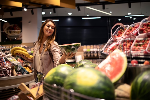 Vrouw die voedsel koopt bij supermarkt