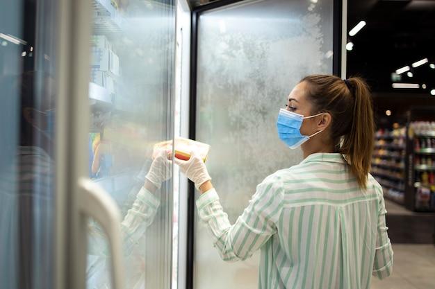 Vrouw die voedsel koopt in de supermarkt en zichzelf beschermt tegen een zeer besmettelijke pandemie van het coronavirus