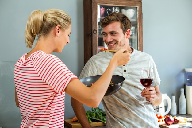 Vrouw die voedsel met echtgenoot in keuken voorbereidt
