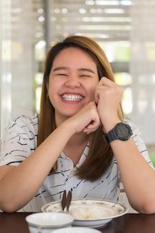 Vrouw die voedsel op eettafel in restaurant eet