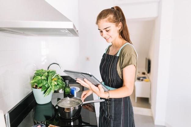 Vrouw die voedsel voorbereidt door het recept in de digitale tablet te kijken
