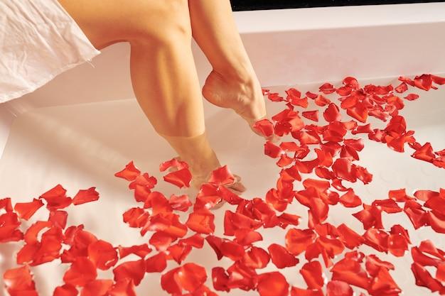 Vrouw die voeten in bad met roze bloemblaadjes zet