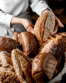 Vrouw die volkorenbroodbroodje onder andere broden zetten