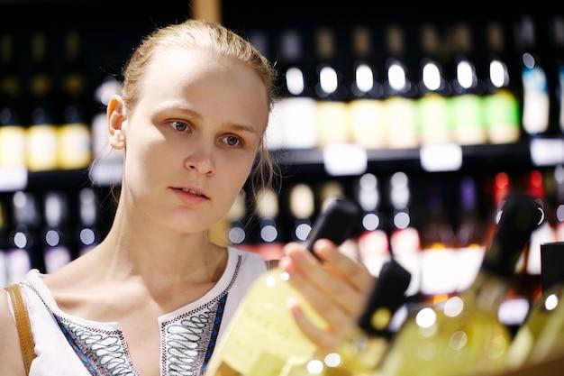 Vrouw die voor alcohol in een flessenopslag winkelt