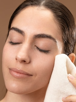 Vrouw die voor haar gezicht zorgt