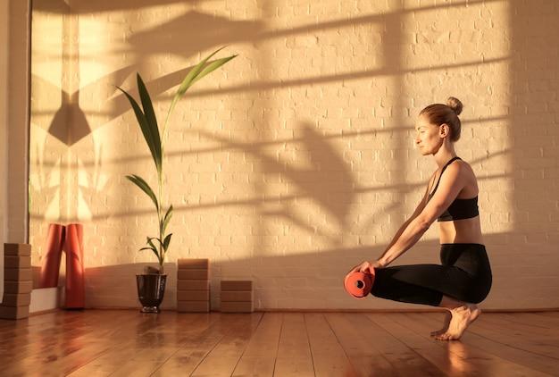 Vrouw die voor het doen van yoga voorbereidingen treft, die een mat op de vloer ligt
